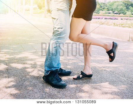 Couple In Relationship Kissing Together While A Girl Lifting Her Leg Up