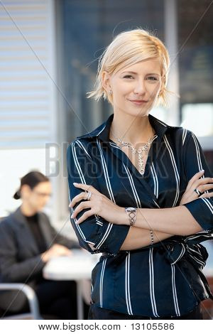 Portrait of attractive young businesswoman standing arms crossed, smiling.