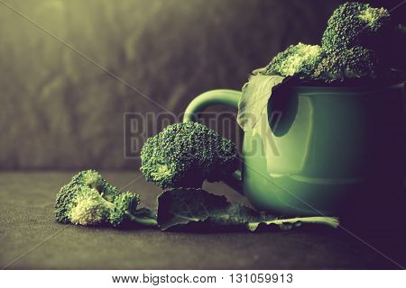 The still life with fresh green broccoli in ceramic cup on black stone plate vintage retro color tone