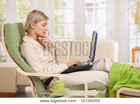 Woman sitting in armchair with feet up working with computer at home in living room.