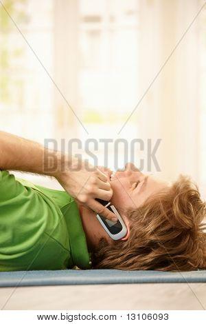 Junge glücklich Kerl am Boden liegen, am Handy sprechen, lachen.