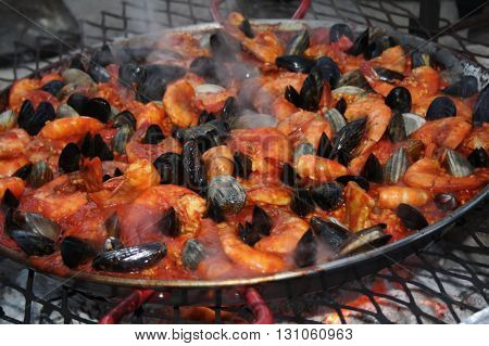 Paella steaming in a large pan over an outdoor grill: shrimp, mussels, clams, and red sauce.