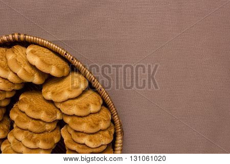 Cookies in a wicker basket on a brown background