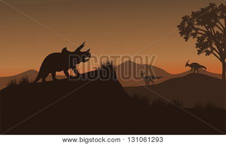 Triceratops and Eoraptor silhouette in hills at afternoon