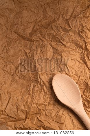 top view of wooden spoon on crumpled brown paper