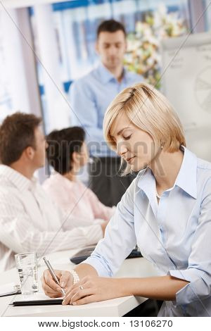 Young businesswoman sitting at table in meeting room writing notes.