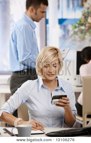 Young businesswoman sitting at office desk, using smart mobile phone.
