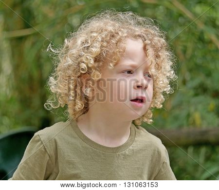 a little boy with blond hair and curly