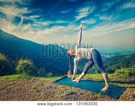 Vintage retro effect hipster style image of woman doing Ashtanga Vinyasa yoga asana Utthita trikonasana - extended triangle pose outdoors in mountains in the morning