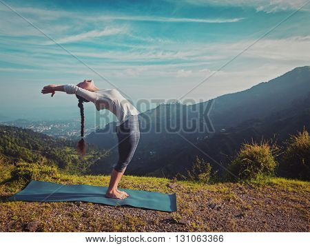 Vintage retro effect hipster style image of young sporty fit man doing yoga Sun salutation Surya Namaskar pose Hasta Uttanasana outdoors in mountains