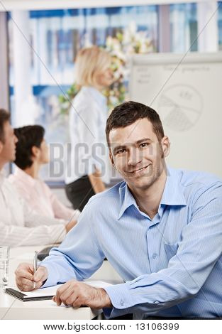 Happy businessman sitting at table in office writing notes on business meeting, looking at camera, smiling.?