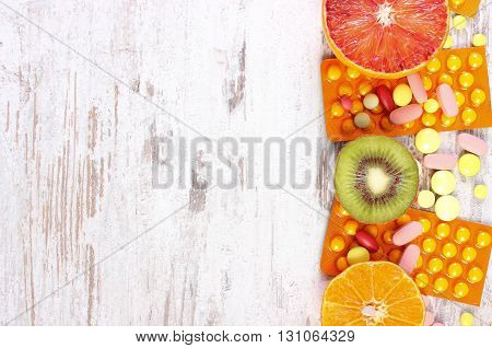 Fresh natural fruits and pills tablets or capsules choice between healthy nutrition and medical supplements copy space for text