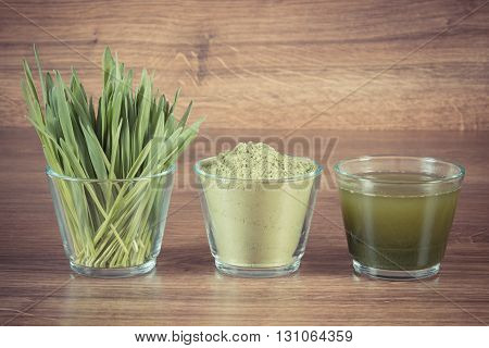 Vintage photo Heap of young powder barley barley grass and beverage on wooden background healthy nutrition and lifestyle body detox