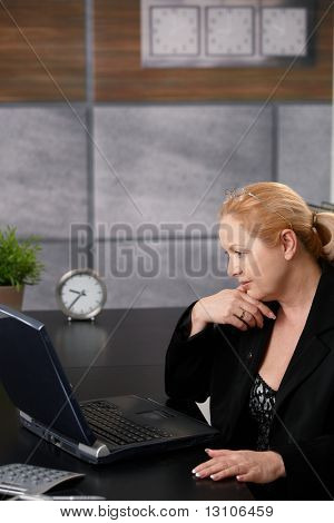 Senior businesswoman working on computer, typing on keyboard, looking at screen, smiling in office.?
