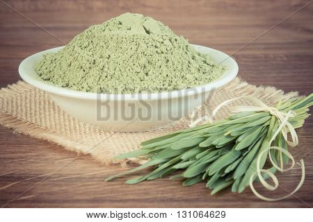 Vintage photo Barley grass with young powder barley in glass dish on jute canvas wooden background healthy nutrition and lifestyle body detox