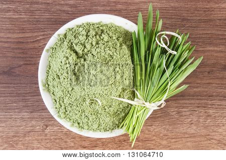 Barley grass with heap of young powder barley in glass bowl on wooden background healthy nutrition and lifestyle body detox