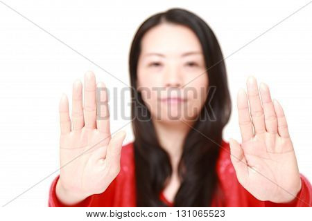 portrait of Japanese woman making stop gesture on white background