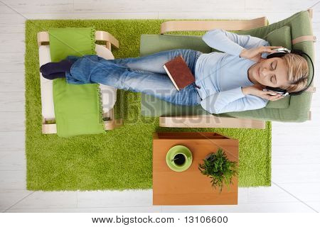 Woman sitting at home with legs crossed on footboard listening to music on headphones with book in lap, eyes closed in overhead view.