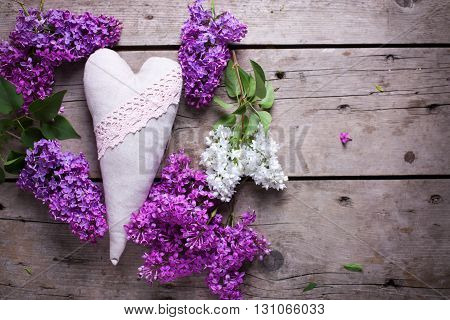 Decorative heart and white and violet lilac flowers on aged wooden planks. Selective focus. Place for text.