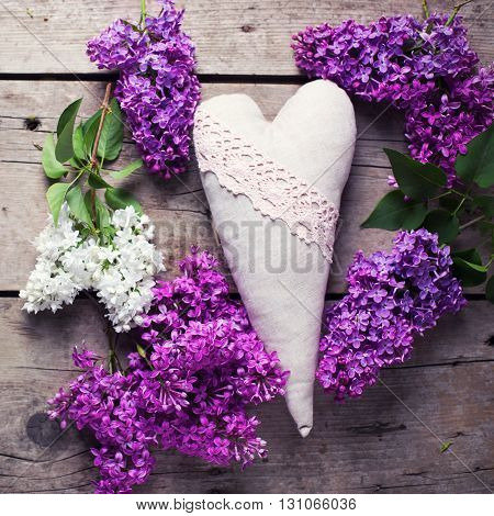 Decorative heart and white and violet lilac flowers on aged wooden planks. Selective focus. Square image. Toned image.