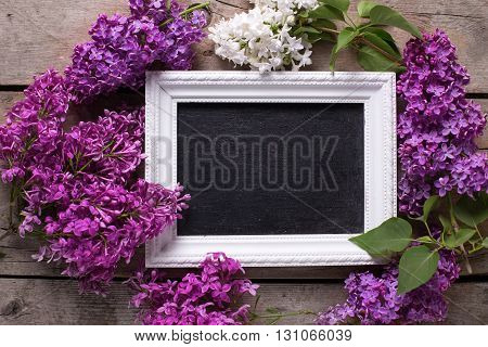 Background with empty blackboard and fresh white and violet lilac flowers on aged wooden planks. Selective focus. Place for text. Flat lay.