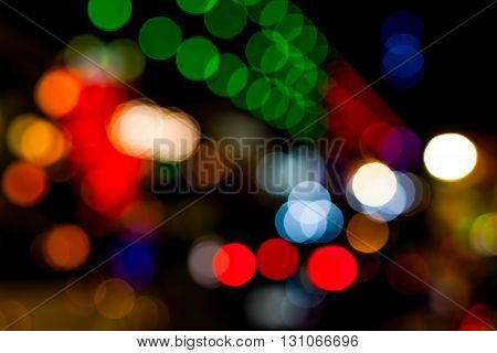 Bokeh of lights on buildings along the sidewalks .