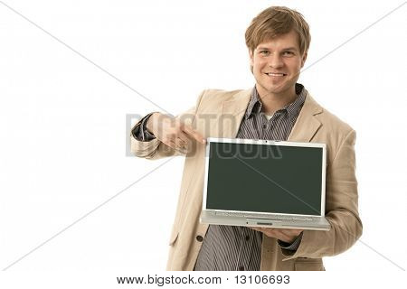 Smiling young man holding laptop computer pointing to blank screen. Copyspace, cutout .