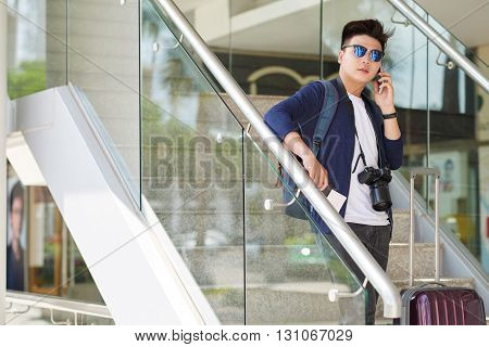 Professional Asian photographer talking on phone when standing in airport