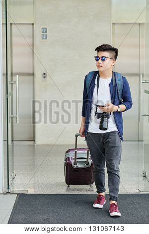 Young Vietnamese traveler with suitcase leaving airport