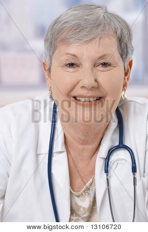 Closeup portrait of happy senior doctor wearing stethoscope, smiling.