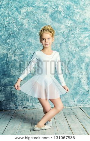 Beautiful young ballet dancer posing in studio.