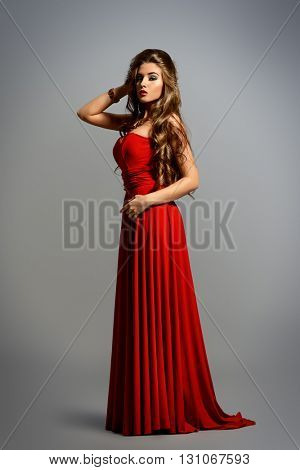 Full length portrait of a beautiful sexy woman with evening make-up and magnificent long hair wearing red dress. Luxurious style. Jewellery.