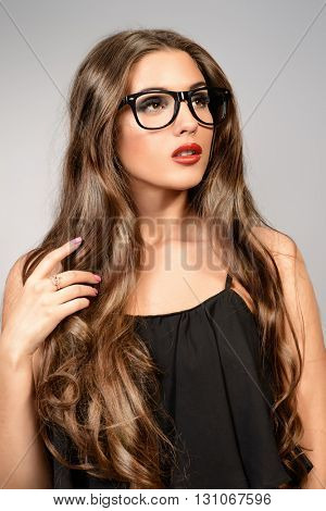Optics style. Beautiful sexy girl with long wavy hair wearing glasses. Fashion studio shot. Cosmetics, make-up. Red lipstick.