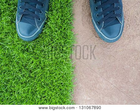 Top View of Two Feet Standing on the Lawn Between the Cement Floor Nature or Building Concept Nature or Man Made Concept Copy Space Horizontal