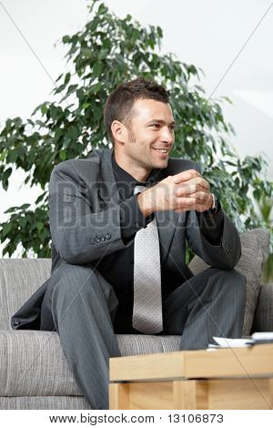People at office. Businessman sitting on sofa, listening to business partner. Low angle view.