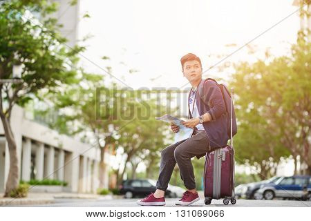 Traveler with city map sitting in the street