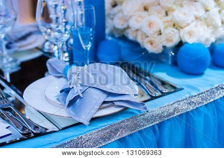 decor for a wedding in the style of blue flowers and candles.