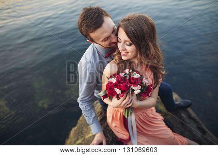Wedding couple kissing and hugging on rocks near blue sea.