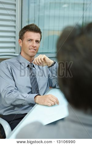Happy young businessman sitting outdoor on office terrace and talking, smiling. Over the shoulder view.