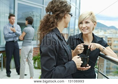 Businesswomen having break on office terrace outdoor drinking coffee talking.
