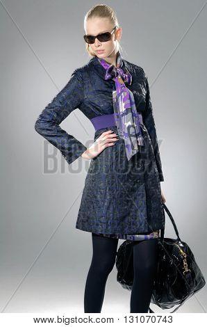 fashion model in autumn/winter clothes holding handbag posing