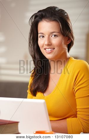Teenage girl looking at camera smiling sitting at table with hands folded under chin.