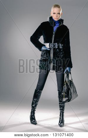 full-length fashion girl with handbag posing on light background
