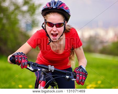 Portrait of bikes cycling girl. Girl rides bicycle at blue sky. Girl in cycling. Bicycling girl coming from  hill and shout.