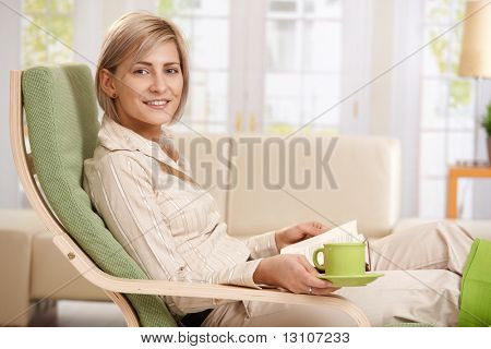Woman relaxing in armchair at home, reading book , holding coffee cup.