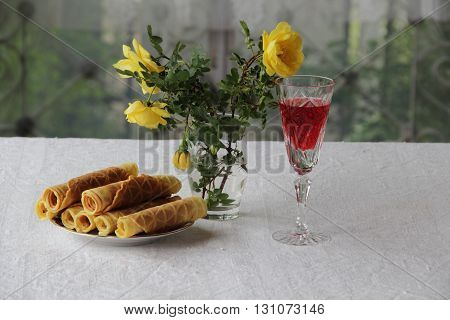 red wine in a glass waffles and a bouquet of yellow roses