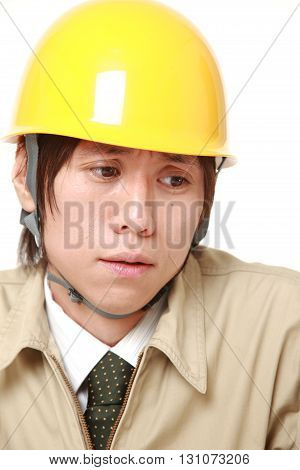 portrait of sad young Japanese construction worker on white background