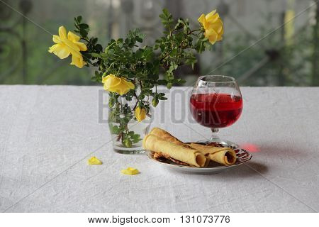 red wine in glass wafer rolls and a bouquet of yellow roses