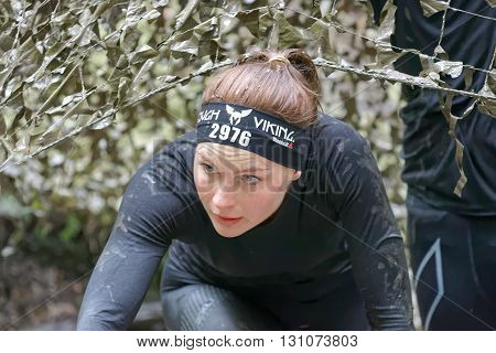 STOCKHOLM SWEDEN - MAY 14 2016: Woman covered with mud crawling under a camouflage net in the obstacle race Tough Viking Event in Sweden April 14 2016