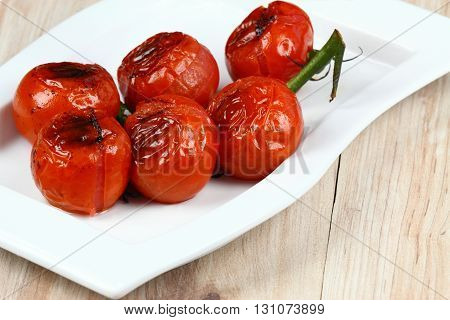 Grilled tomatoes. Bunch of tomatoes. Tomatoes on the plate. Ripe tomatoes. Barbecue vegetable.